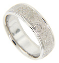 Floral patterns on a matte finish decorate the center of this 14K white gold antique style mens wedding band