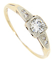 A .24 carat diamond is set in the center of this antique 14K bi-color gold engagement ring