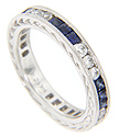 Trios of faceted round diamonds alternate with faceted square cut blue sapphires on this 14K white gold stackable wedding band