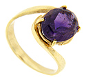 A deep purple oval amethyst is held by wrap around arms on this 14K yellow gold estate ring