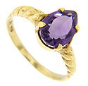 A deep purple pear shaped amethyst is set in this spiraling 18K yellow gold estate ring