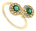 Two round, sparkling green emeralds are surrounded by rings of diamonds on this 14K yellow gold ring