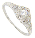 A trio of diamonds is set over a single diamond on each shoulder of this platinum antique style engagement ring