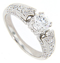 A glittering array of round diamonds are set in the shoulders and sides of this contemporary engagement ring