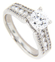 A double row of round diamonds flanks a central line of diamonds on each shoulder of this contemporary engagement ring