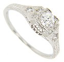 Trios of diamonds are set in the shoulders of this platinum antique style engagement ring