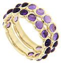 Cabochon purple amethysts are set three quarters of the way around these 14K yellow gold stackable wedding bands