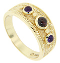 A cabochon garnet is flanked by two cabochon purple amethysts on this 14K yellow gold estate wedding band