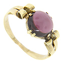 A round cabochon rhodalite garnet is set in the center of this 14K yellow gold antique ring