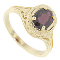 This antique style 14K yellow gold ring is set with a faceted oval garnet