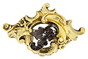 Asymmetrical in design, this antique pinchbeck pin features a flowing Biedermeier pattern realized in garnets and seed pearls