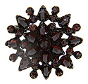 Contrast between pointed pear garnets and faceted round garnets decorates this antique style sterling silver pin's outer edge