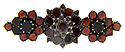 Three interconnected groups of table cut pyrope garnets are used to create this antique pin