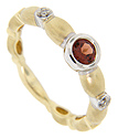 A single faceted round garnet surround by a ring of white gold is at the center of this 14K yellow gold wedding band