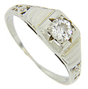 Stepped shoulders and floral designs decorate the sides of this 14K white gold art deco engagement ring