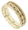 A repeating floral design spans the circumference of this 14K yellow gold vintage wedding band