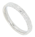 A flowing flower and vine motif decorate the top and sides of this 14K white gold antique style wedding band