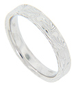 Curving floral engraved designs cover the top and sides of this 14K white gold antique style wedding band