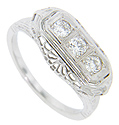 Three European cut diamonds are set in a row across the top of this 14K white gold antique wedding band