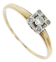 A single round diamond set in a white gold head decorates this 14K yellow gold retro-modern engagement ring