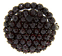Faceted round garnets are set in a tightly packed circle surrounded by a concentric ring on this antique garnet pin