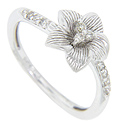 Five petals with engraved detailing cradle a trio of diamonds in the center of this 14K white gold antique style floral engagement ring
