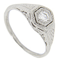 Beautiful filigree and engraving adorns the sides of this antique style platinum and diamond engagement ring