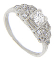 The central .33 carat diamond in this antique style platinum engagement ring rests in a slightly raised setting that lets the diamond catch the light