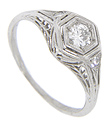 A lovely, sweeping leaf design is worked on the sides of this platinum antique style engagement ring while delicate filigree runs down the shoulders