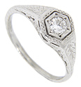 Ornate engraving ornaments the shoulders of this platinum antique style engagement ring