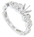 Diamonds are set in floral designs on the shoulders of this antique style 14K white gold engagement ring mounting