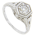 Heart patterns adorn the shoulders of this 14K white gold antique style engagement ring