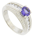Crafted of 14K white gold, this tanzanite and diamond modern engagement ring is set with a round tanzanite measuring approximately .90 carats