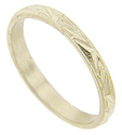 Raised triangular shapes decorate the circumference of this 14K yellow gold antique style wedding band