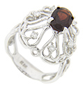 A faceted oval garnet is surrounded by sparkling round diamonds on this vintage 14K white gold ring
