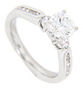 A single round diamond rests on either side of the center stone on the engagement ring in this contemporary wedding set