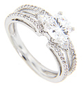 Double rows of round diamonds and two pear-shaped diamonds frame the round center stone on this contemporary engagement ring