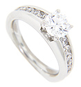 Channel set round diamonds ornament the shoulders of the engagement ring in this contemporary wedding set