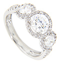 Rings of round diamonds surround the three larger round diamonds on the engagement ring in this contemporary wedding set