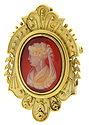 Crafted of stone and set in a 14K yellow gold frame, this antique cameo depicts a woman in profile