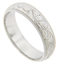 Looping floral patterning and milgrain designs cover this 14K white gold antique style men's wedding band
