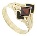 A garnet faceted in a diamond shape and flanked by chevrons of black onyx ornament this 14K yellow gold antique style ring