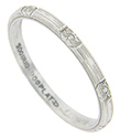 Floral designs are spaced around the circumference of this antique platinum wedding band