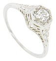 Engraved leaf patterns adorn the shoulders of this 18K white gold antique style engagement ring