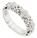 Groups of diamonds and matte finish looping designs decorate this 14K white gold antique style wedding band