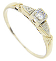 A single faceted round diamond is set in this 14K yellow gold antique engagement ring