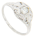The geometric top of this 14K white gold antique engagement ring holds a .22 carat H color Is clarity round diamond