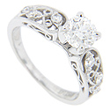 Trios of diamonds are interspersed with looping designs on the shoulders of this platinum antique style engagement ring mounting