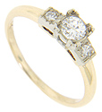 A .27 carat, H color Si1 clarity diamond rests in the center of this 14K bi-color gold vintage engagement ring