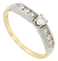 Three channel set diamonds ornament each shoulder of this 18K bi-color gold retro-modern engagement ring